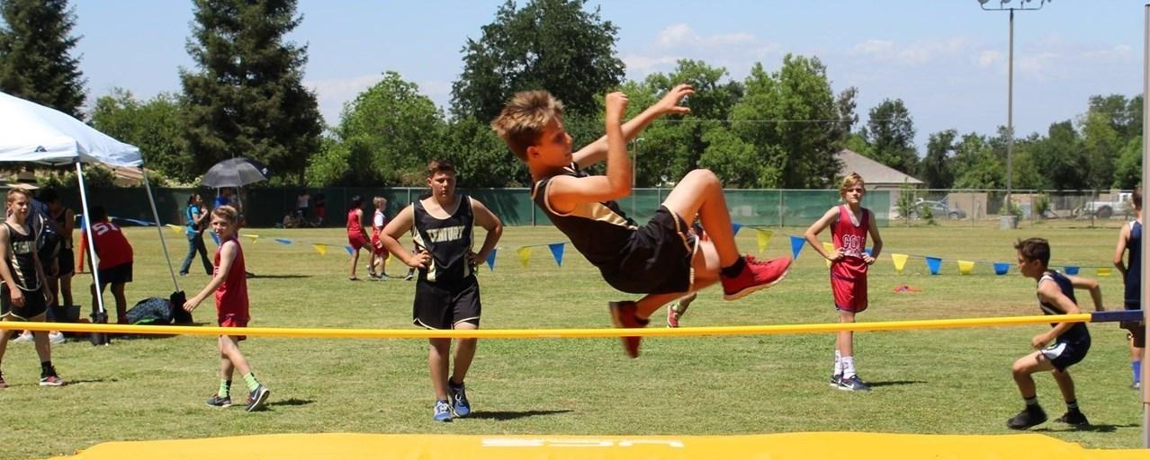 Boy Jumps over the bar on teh high jump